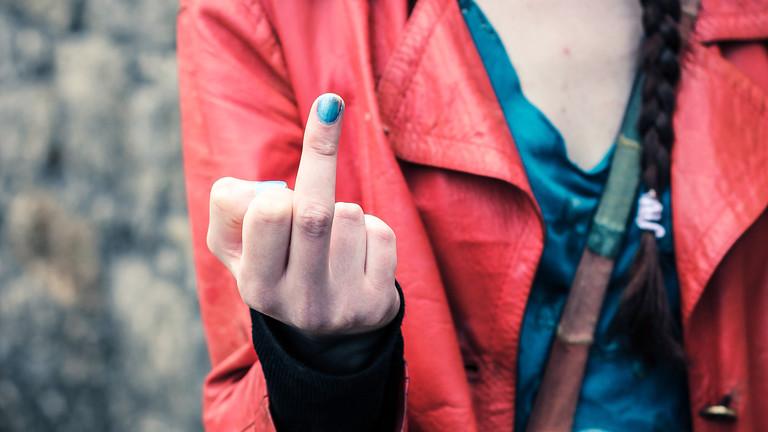 Frau zeigt den Mittelfinger