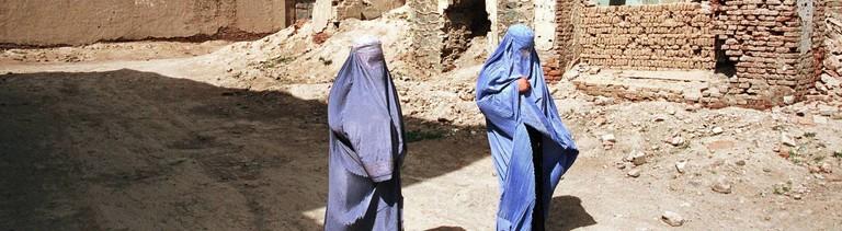 Frauen in Burka in einem zerstörten Ort.