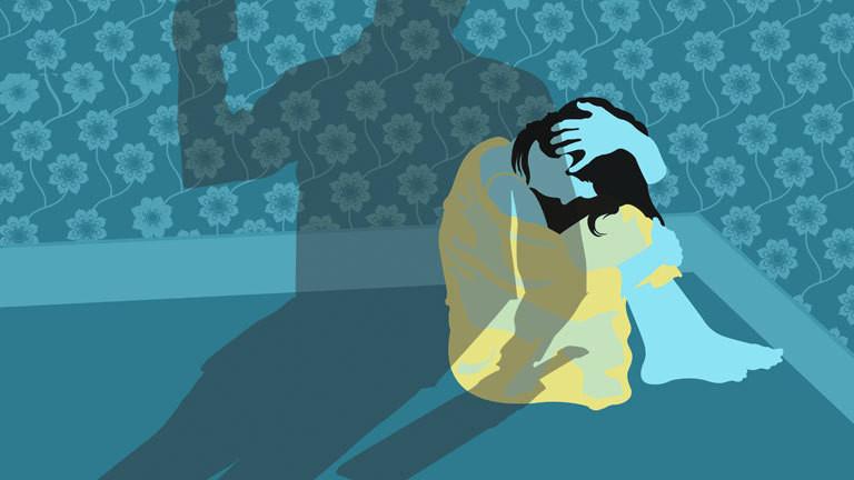 Symbolbild: Gewalt gegen eine Frau, die in der Ecke eines Zimmers kauert