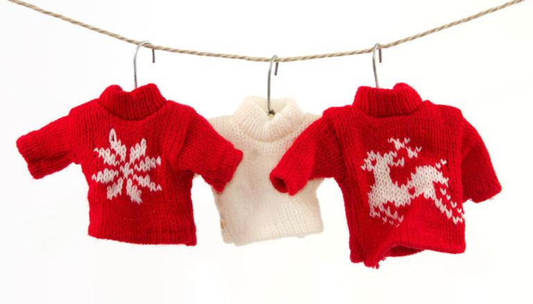Miniatur-Pullover an einer Wäscheleine.