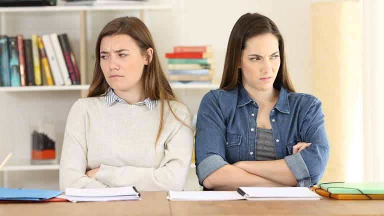 Zwei ärgerlich dreinschauende Frauen an einem Schreibtisch, mit verschränkten Armen, voneinander wegschauend.