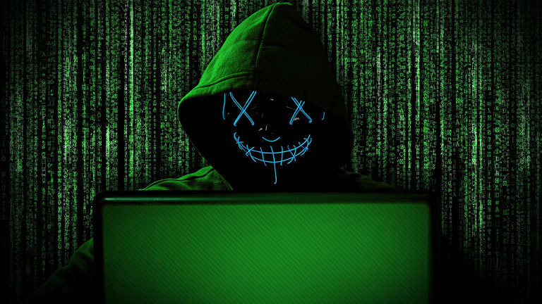 Cyberkriminalität: Ein Hacker mit einer leuchtenden Maske hinter einem Laptop. Im Hintergrund ist Binärcode zu sehen.