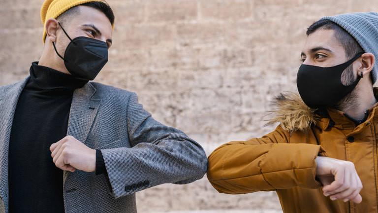 Zwei Männer mit Masken begrüßen sich mit dem Ellbogen.