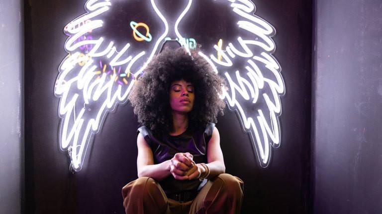 Eine Frau sitzt vor einer beleuchteten Flügel-Installation.