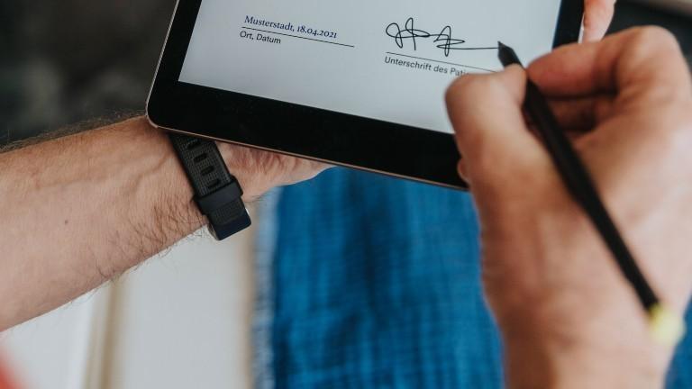 Ein männlicher Patient unterschreibt einen Antrag beim Arzt.