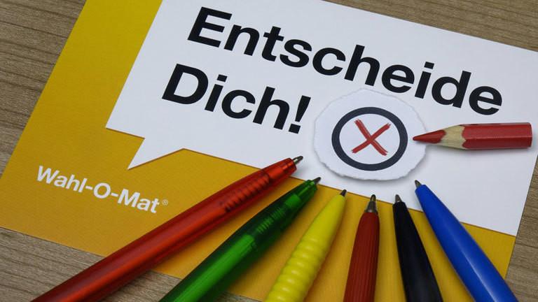 Wahl-O-Mat und Kugelschreiber in den Parteifarben.