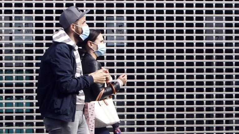 Fußgänger - ein Paar läuft an einem heruntergelassenen Ladengitter eines geschlossenen Geschäftes vorbei.