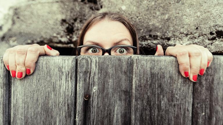 Frau guckt über eine Mauer