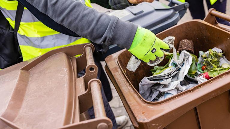 Ein Abfall-Scort checkt den Inhalt einer Biotonne.