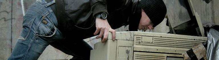 Mann auf der Müllhalde mit altem Kopiergerät
