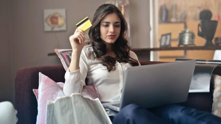 Frau sitzt auf dem Sofa, hält eine Kreditkarte in der hand und den Laptop auf dem Schoß.