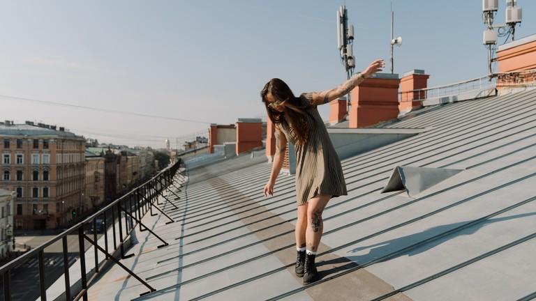 Eine Frau balanciert auf einem Dach