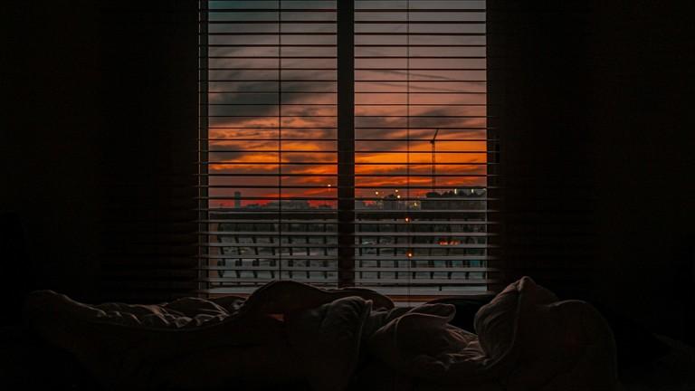 Ungemachtes Bett vor einem Fenster, dahinter geht die Sonne auf. Oder die Sonne geht unter.
