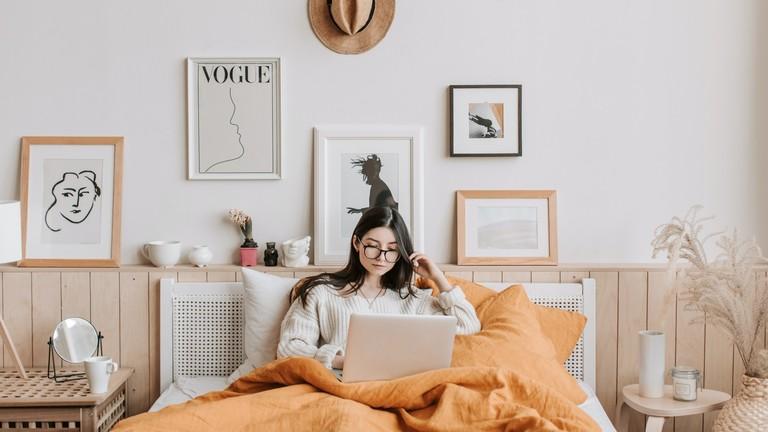 Eine Frau sitzt mit ihrem Rechner im Bett und schaut vielleicht eine Serie oder einen Film