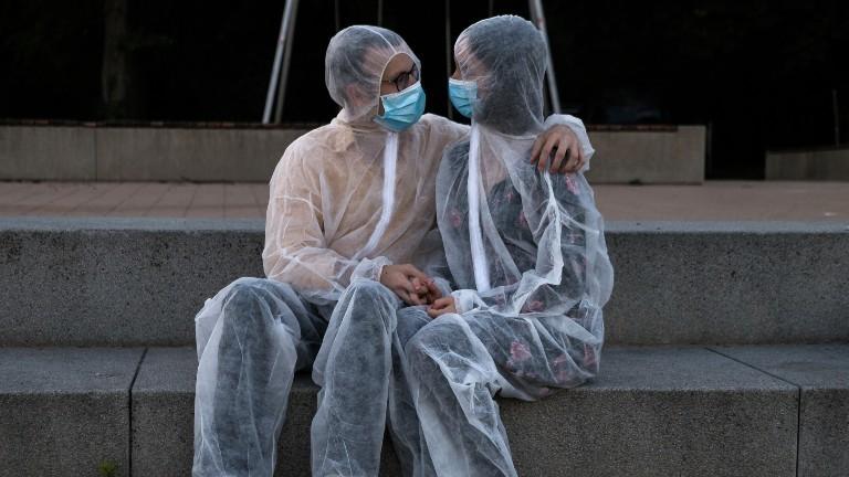Ein Pärchen trägt Schutzanzüge, Masken und umarmt sich.