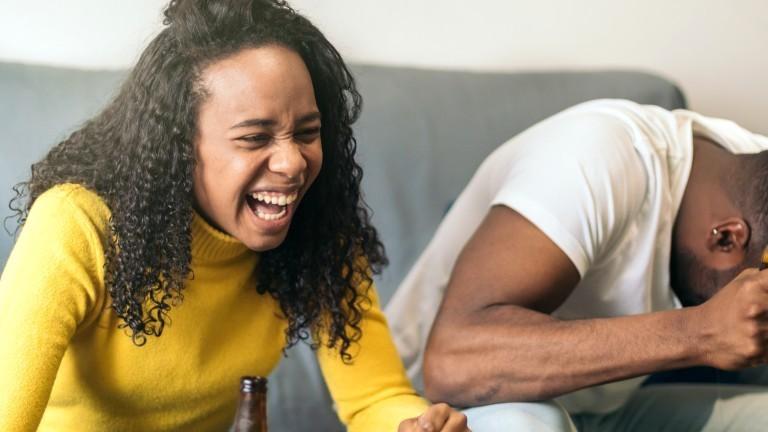 Eine Frau und ein Mann sitzen auf einer Couch und lachen sich kaputt