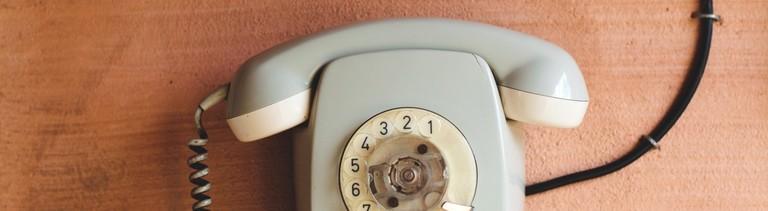 Ein altes graues Telefon mit Wählscheibe hängt an einer Ocker gestrichenen Wand.