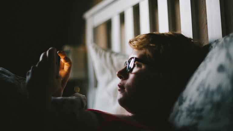 Junge liegt im Bett und starrt auf sein Handy
