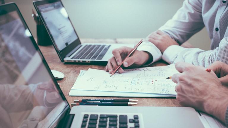 Zwei Männer sitzen an ihren Laptops und schreiben Notizen auf ein Blatt Papier.