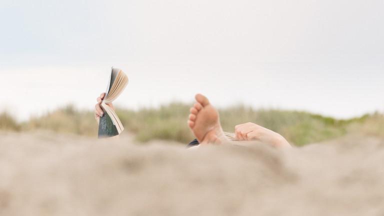 Ein Mann oder eine Frau liest ein Buch am Strand.