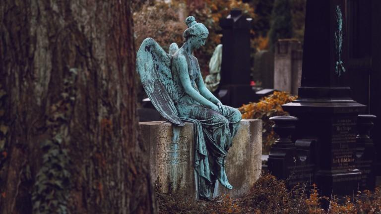 Die Statue eines Engels auf einem Grabstein.