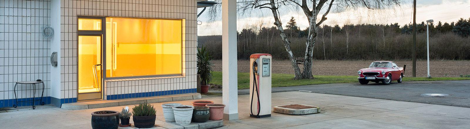 beleuchtete Tankstelle, Oldtimer im Hintergrund
