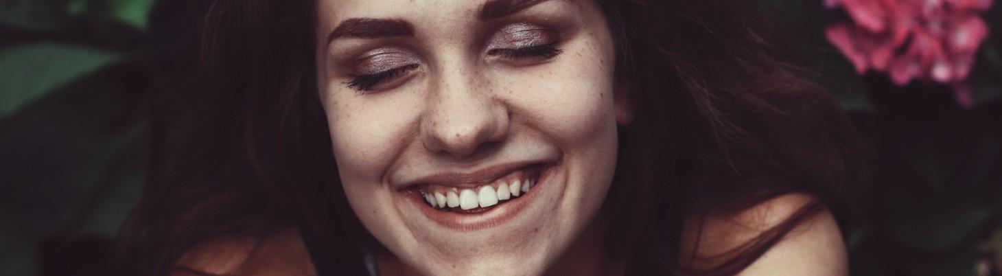 Frau sitzt in einem Blumenbeet und lächelt