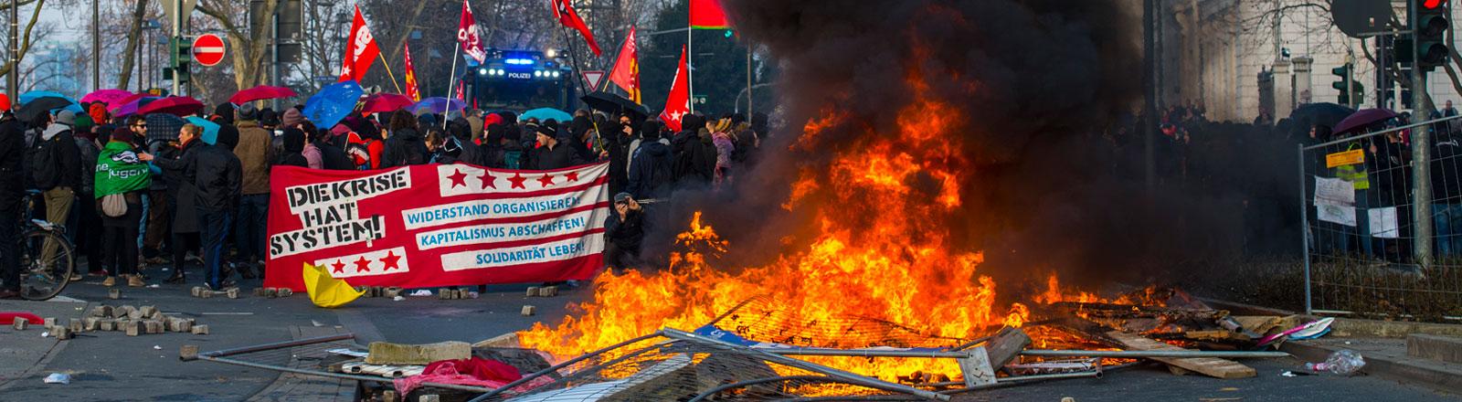 brennende Materialien auf der Straße im HIntergrund unbeteiligte Demonstranten mit Plakaten und Fahnen