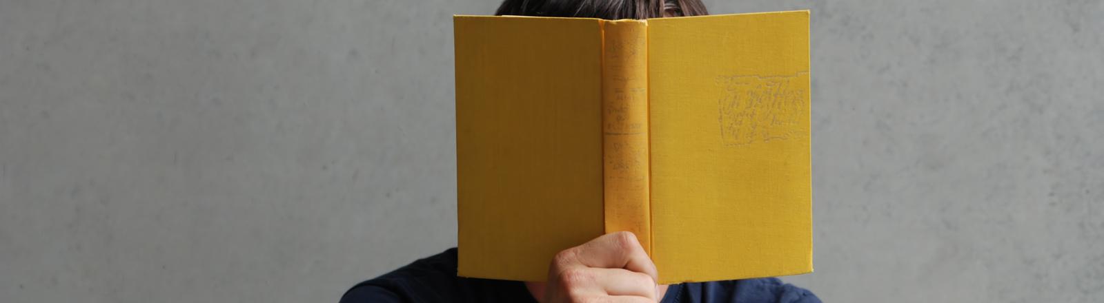 Mann hält sich ein Buch vor das Gesicht