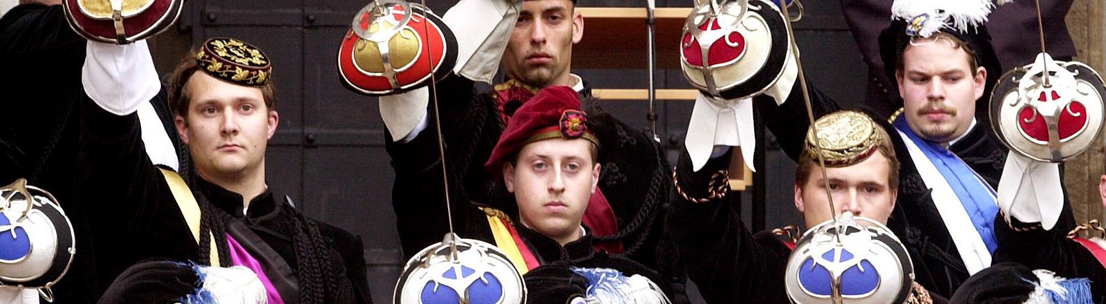 Männer posieren mit Uniform und Säbel.