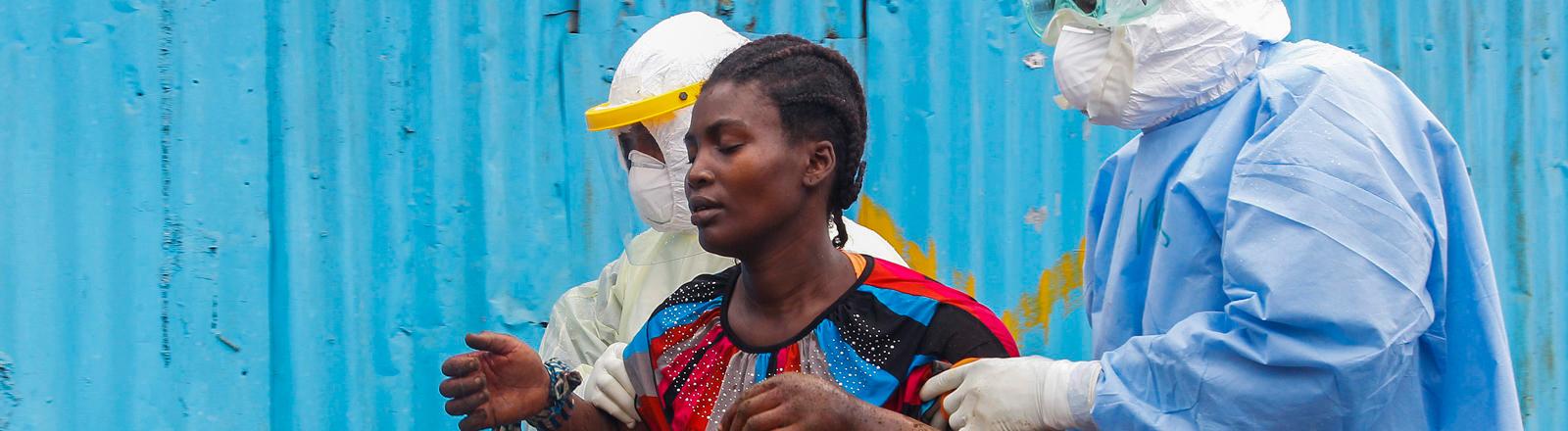 Zwei Helfer stützen eine an Ebola erkrankte Frau in Liberia