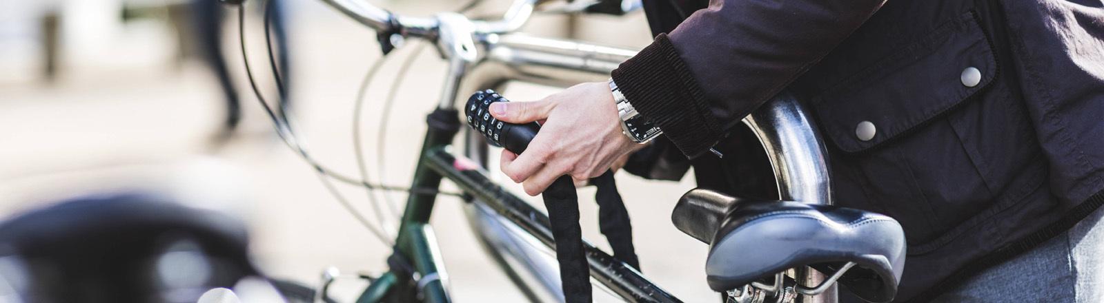 Eine Person schließt ein Fahrrad mit einem Schloss an, um es zu sichern.