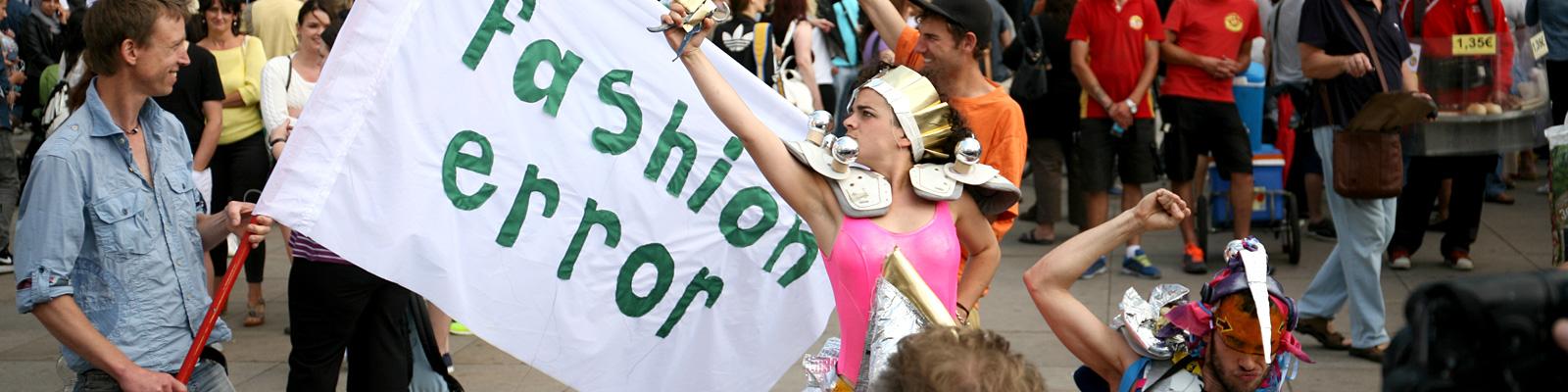 """""""Fashion Error"""" steht auf einem Plakat einer Demo."""