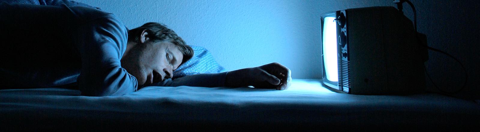 Mann schläft vor dem Fernseher