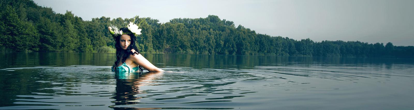 Frau mit Blume im Haar steht im Wasser