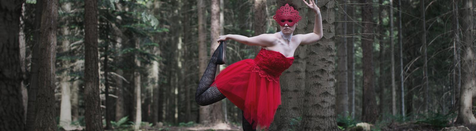 Maskierte Frau tanzt im Wald