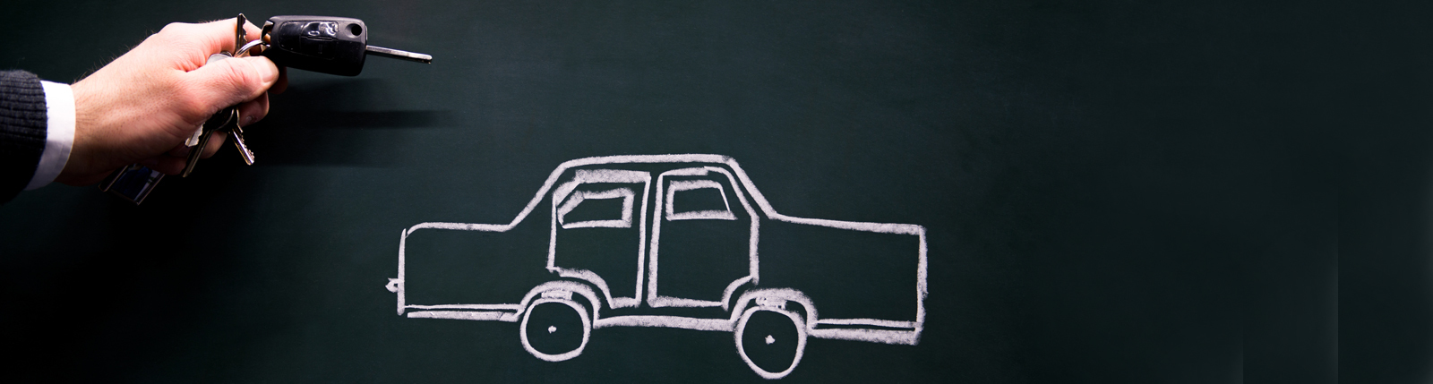 Auto auf Tafel gemalt, Mann hält Schlüssel daneben