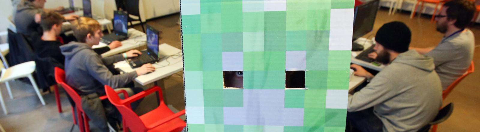 """Ein Teilnehmer des Computer-Festivals play13 posiert in Hamburg mit einem aus Pappe nachgebauten Würfel des Computerspiel """"Minecraft""""."""