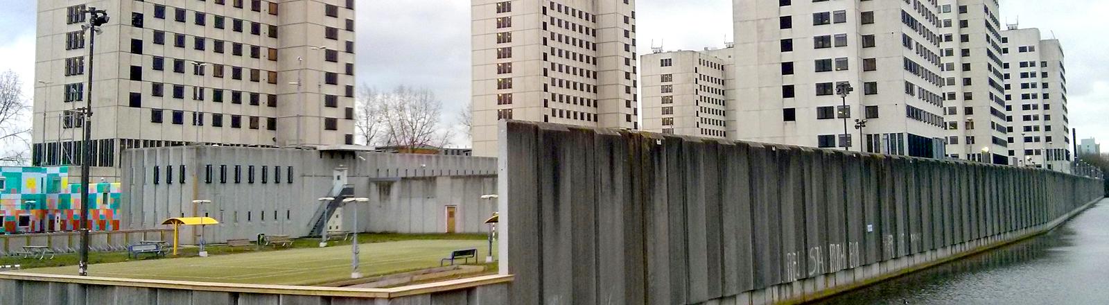 Hochhäuser mit einer dicken Mauer drumherum.