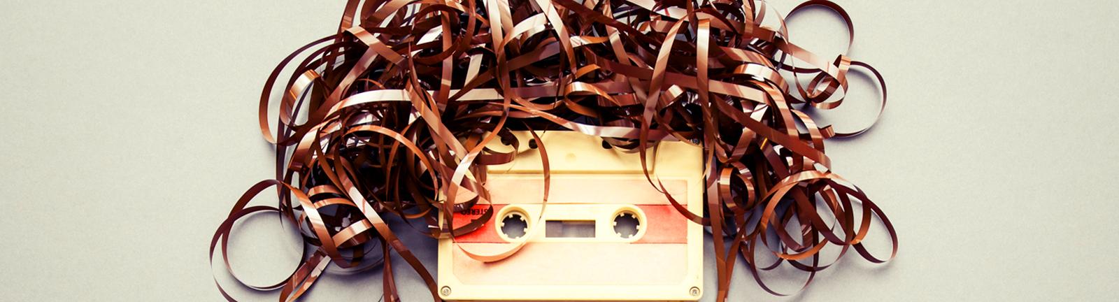 Kassette mit Tonband-Wirrwarr sieht auch wie ein Kopf mit Haaren.