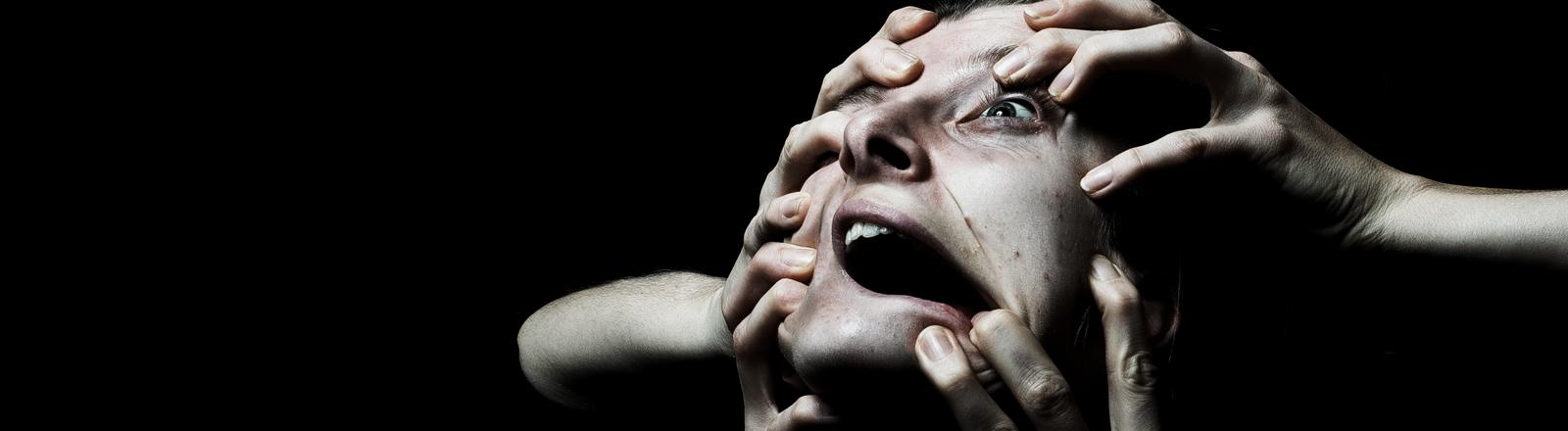 Mehrere Hände packen einer Frau ins Gesicht.