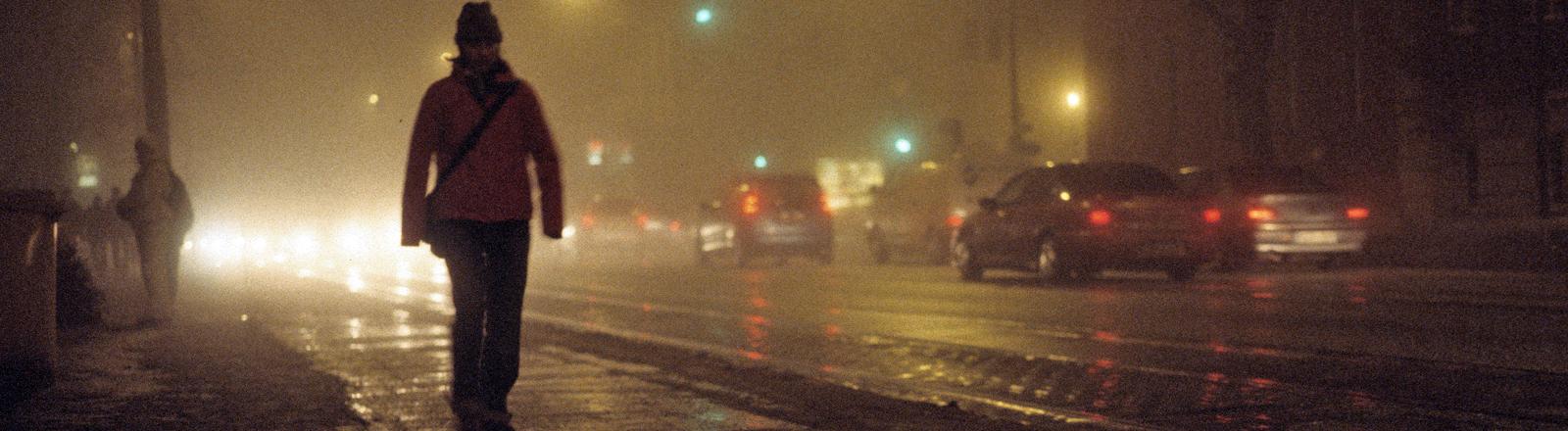 Eine Person läuft nachts durch Berlin.