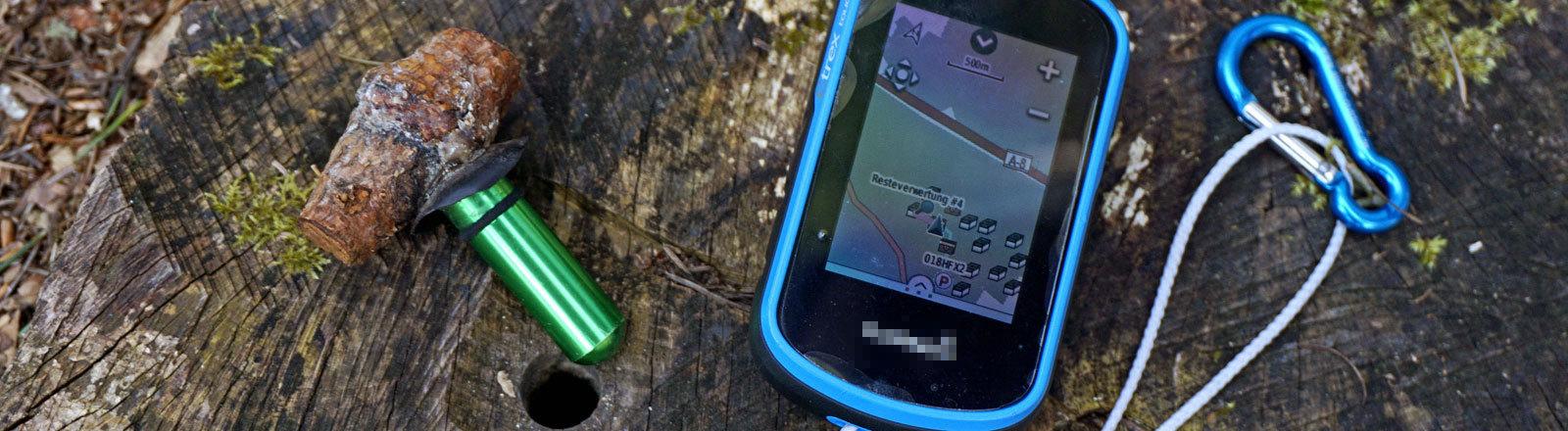 Ein GPS-Empfänger und ein Geocache, das mit einem Stück Holz getarnt wurde.