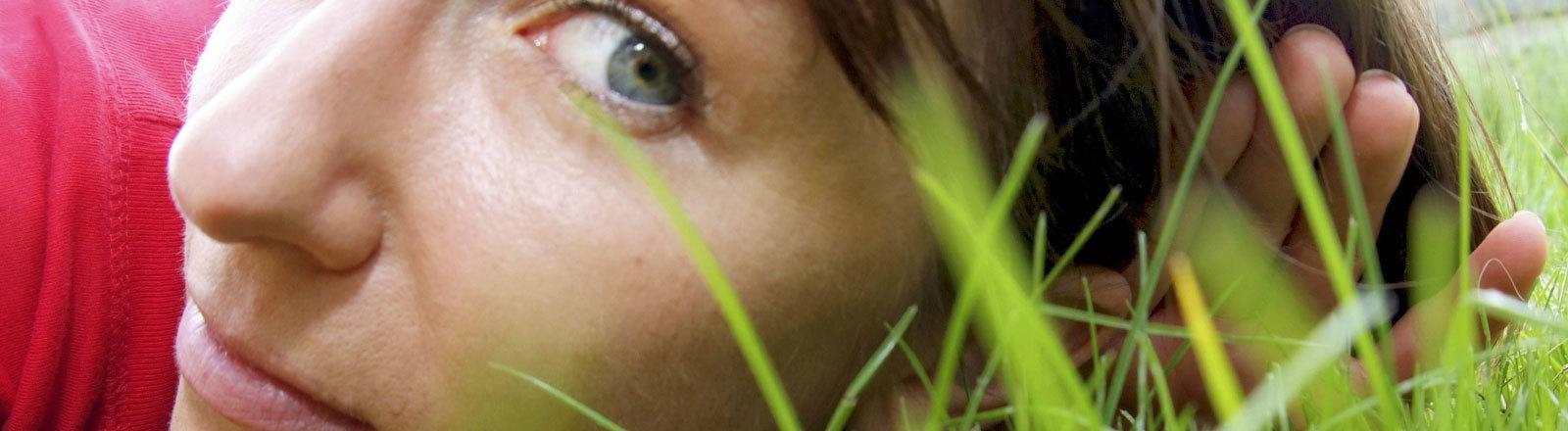 Junge Frau liegt auf einer Wiese und hört dem Gras beim Wachsen zu.