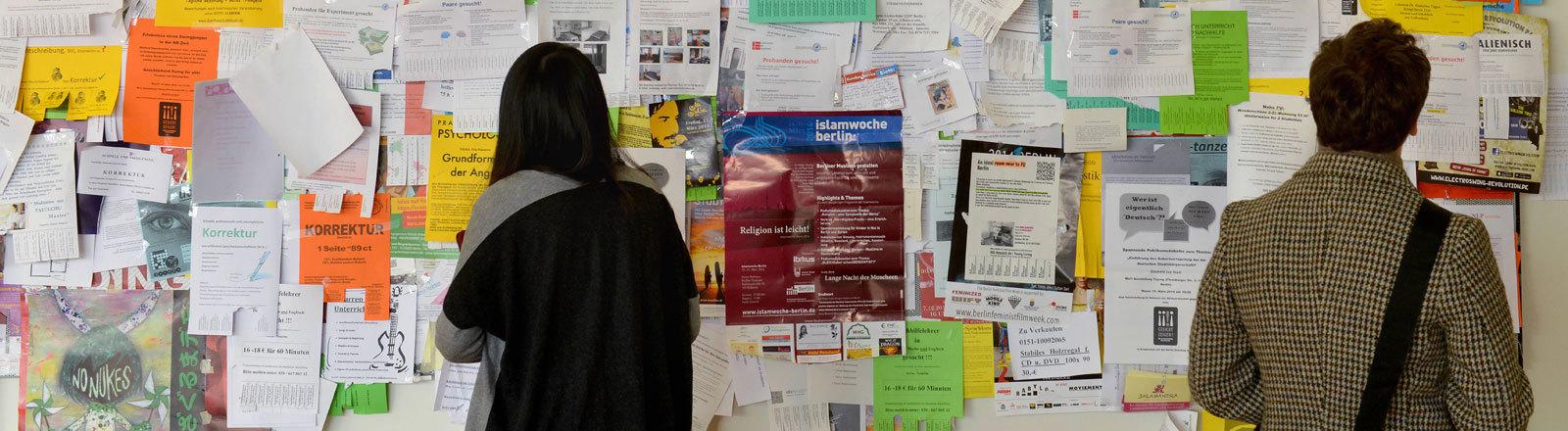 Zwei Studierende suchen an einem Schwarzen Brett nach Angeboten.
