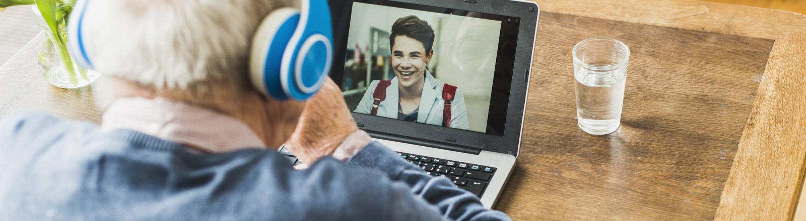 Ein älterer Herr führt ein Gespräch per Videocall mit einem jüngeren Mann.
