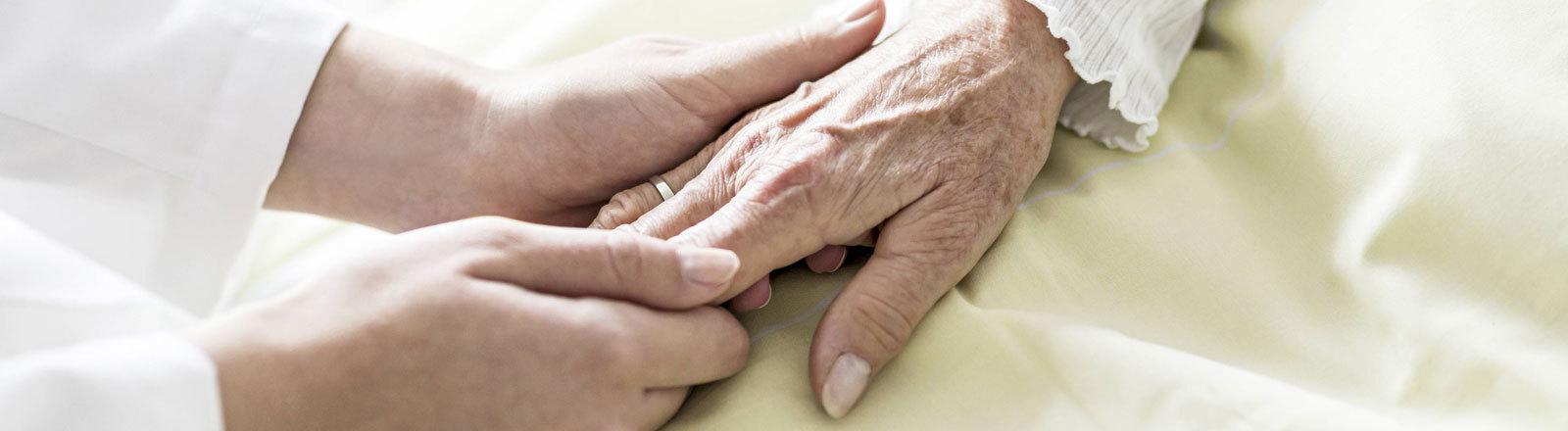 Pflegerin hält die  Hand einer Seniorin.