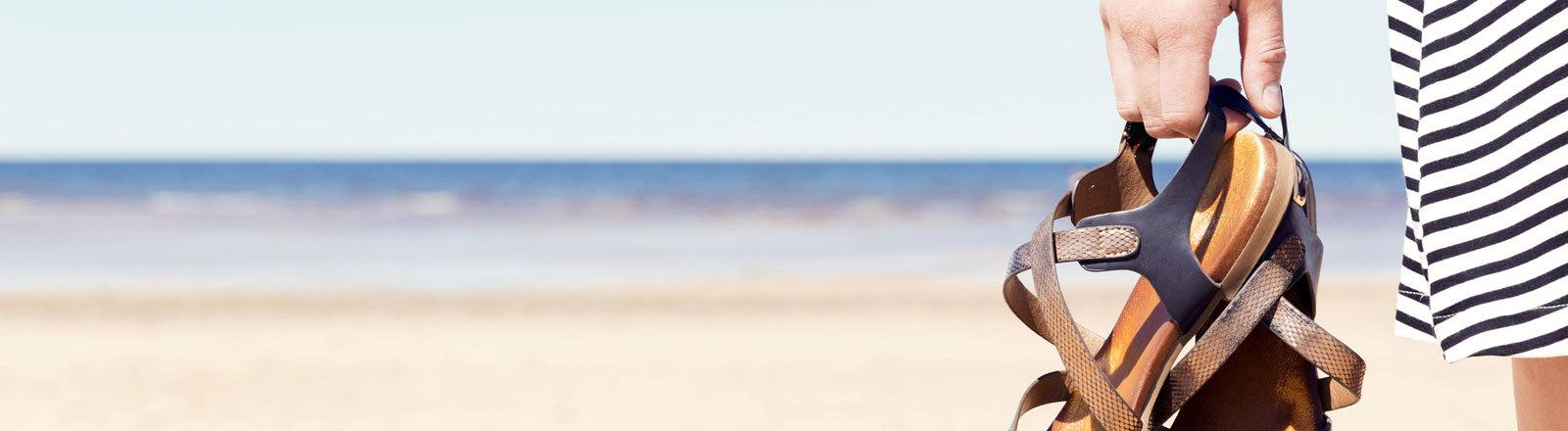 Am Strand: Eine Frau hält Sandalen in der Hand