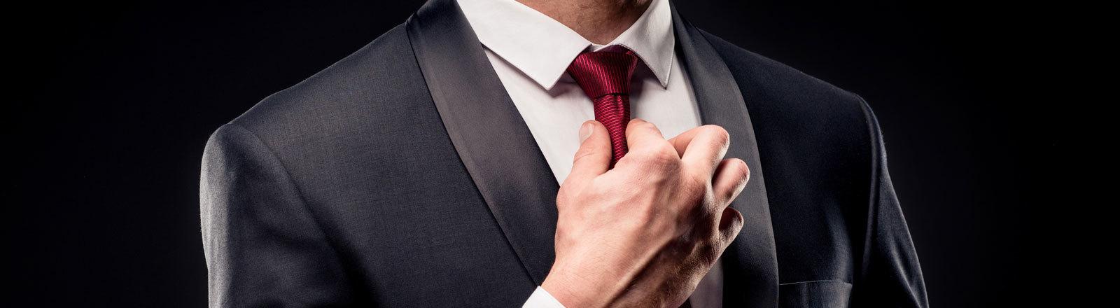 Ein Mann zieht seine Krawatte zurecht.