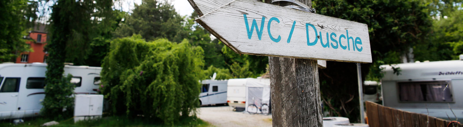 Campingplatz mit Wegweisern, die die Richtung zu den Plätzen, Duschen und Toiletten weisen.